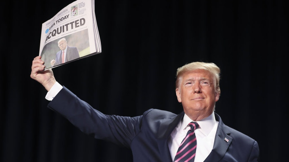 """U.S. President Donald Trump holds up a copy of USA Today newspaper with a banner headline that reads """"Acquitted"""" as he arrives to annual National Prayer Breakfast at the Washington Hilton in Washington, D.C., U.S., on Thursday, Feb. 6, 2020. Trumpused the annual National Prayer Breakfast Thursday to attack his political enemies after his partisan acquittal of impeachment charges. Photographer: Oliver Contreras/Sipa/Bloomberg"""