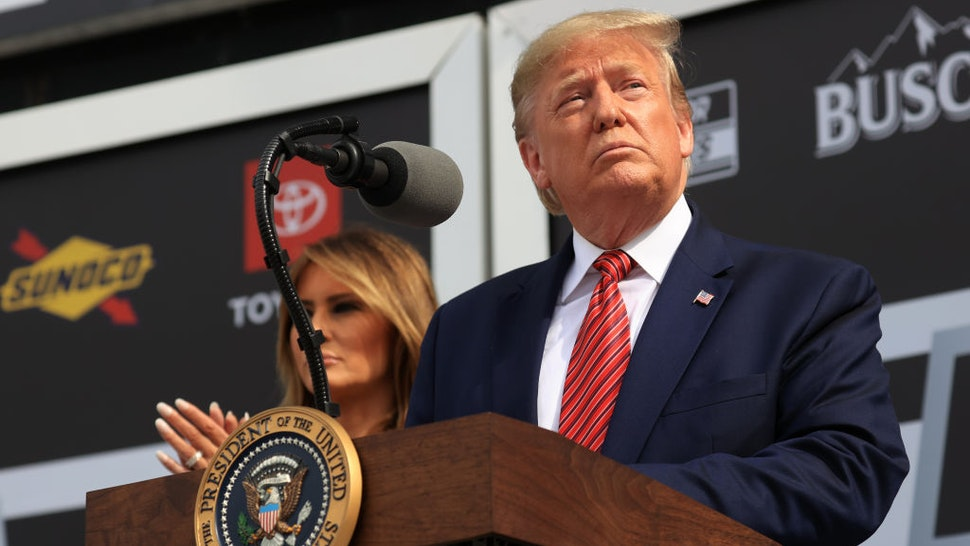 U.S. President Donald Trump speaks as First Lady Melania Trump looks on from Victory Lane prior to the NASCAR Cup Series 62nd Annual Daytona 500 at Daytona International Speedway on February 16, 2020 in Daytona Beach, Florida. (Photo by Chris Graythen/Getty Images)