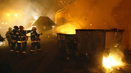 Minneapolis firemen put out a fire in a garbage dumpster in a parking lot next to Starbucks Coffee on the University of Minnesota campus. The fires were set by students rioting after the Gopher hockey team won the national title.