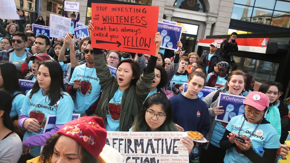 """Sarah Chung, a junior at Harvard University, holding orange sign at center, participates in a """"defend diversity"""" pro-affirmative-action rally in Harvard Square in Cambridge, MA on Oct. 14,. 2018."""