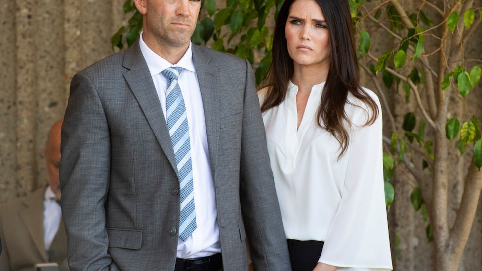 Dr. Grant Robicheaux, and his girlfriend Cerissa Riley listen to their attorney address the press outside the Harbor Justice Center in Newport Beach, CA on Wednesday, October 17, 2018.