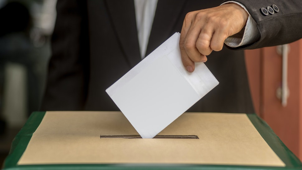 Hand of a person casting a vote into the ballot box during elections - stock photo