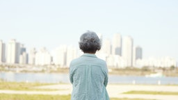 Rear view of senior woman standing by river bank - stock photo