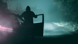 A lone, hooded figure standing next to a car looking at an empty misty winter country road silhouetted at night by car headlights - stock photo