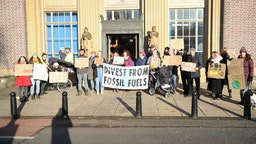 Protesters hold placards and a banner that says divest from fossil fuels during the demonstration.