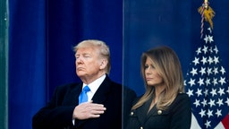 The 45th President Donald J. Trump with his had on his heart and the First Lady Melania Trump with her arms at her side after he addressed the crowd during his opening ceremony of the New York City 100th annual Veterans Day Parade and wreath-laying at the Eternal Light Flag Staff.