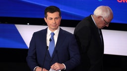 Former South Bend, Indiana Mayor Pete Buttigieg (C) and Sen. Bernie Sanders (I-VT) take a break during the Democratic presidential primary debate at Drake University on January 14, 2020 in Des Moines, Iowa.