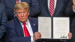 U.S. President Donald Trump ceremonially signs legislation at a rally with local farmers on February 19, 2020 in Bakersfield, California.