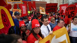 Democratic presidential candidate former South Bend, Indiana Mayor Pete Buttigieg marches with South Carolina McDonald's workers as they demonstrate for a $15 an hour wage and the right to form a workers union February 24, 2020 in Charleston, South Carolina.