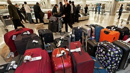 A woman pushes her luggage cart past unclaimed bags inside the US Customs and Border Protection inspection area at Dulles International Airport (IAD), December 21, 2011 in Sterling, Virgina, near Washington, DC.