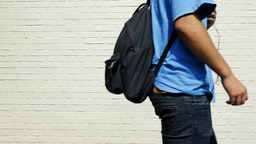 Young male student (with a black backpack, wearing a blue T-shirt and jeans) on his way to school passing an off-white brick wall. Focus is on the wall.