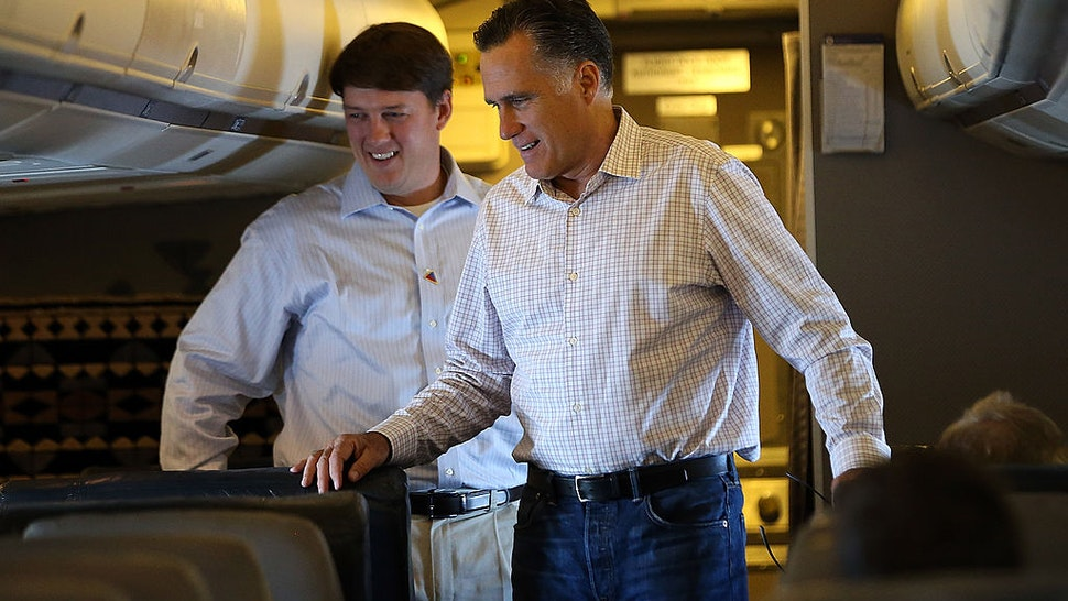 Republican presidential candidate, former Massachusetts Gov. Mitt Romney (R) stands with traveling press secretary Rick Gorka (L) aboard his campaign plane on August 29, 2012 en route to Indianapolis, Indiana.