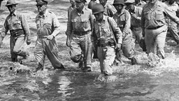 General Douglas MacArthur (second from left) walks to the shore of Leyte Island with a group of U.S. Army and Philippine officers