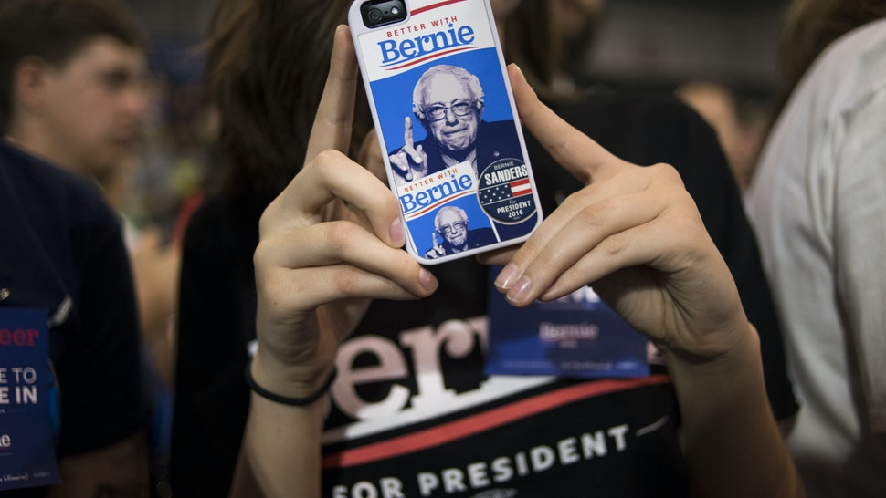 An attendee displays a Senator Bernie Sanders, an independent from Vermont and 2016 Democratic presidential candidate, themed smart phone case during a campaign event in Huntington, West Virginia, U.S., on Tuesday, April 26, 2016. Sanders' single win in Rhode Island out of the five contests held on Tuesday puts his opponent Hillary Clinton on the brink of the Democratic presidential nomination. Photographer: Ty Wright/Bloomberg via Getty Images