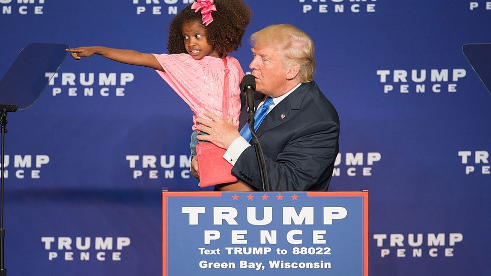 Republican presidential nominee Donald Trump holds a child as he speaks during a rally at the KI Convention Center on October 17, 2016 in Green Bay, Wisconsin.