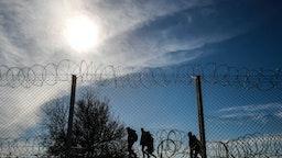 Refugees Running On Border Against Sky - stock photo