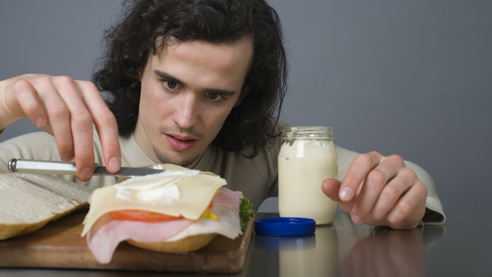 Man putting mayonnaise on a sandwich
