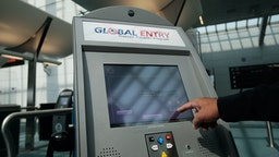 EWARK, NJ - AUGUST 24: An officer with the US Customs and Border Protection demonstrates a new arrivals processing kiosk at Newark International Airport August 24, 2009 in Newark, New Jersey. Officials with U.S. Customs and Border Protection are introducing are introducing the Global Entry program, which allows pre-screening and approval of travelers and faster trips through customs and passport lines upon arriving into the United States. (Photo by Chris Hondros/Getty Images)