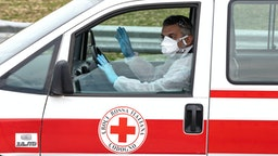 CASALPUSTERLENGO, ITALY - FEBRUARY 23: A member of the Italian Red Cross, wearing a respiratory mask, drives a vehicle on February 23, 2020 in Casalpusterlengo, south-west Milan, Italy. Casalpusterlengo is one of the ten small towns placed under lockdown earlier this morning as a second death from coronavirus sparked fears throughout the Lombardy region.