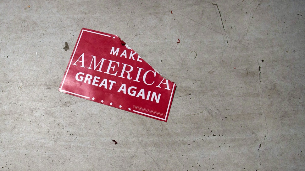 "A ""Make America Great Again"" sign sits on the floor following a campaign rally with the US president at Central Wisconsin Airport in Mosinee, Wisconsin, October 24, 2018."