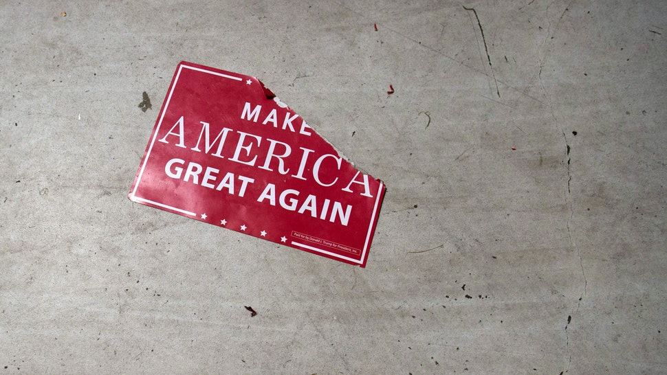 """A """"Make America Great Again"""" sign sits on the floor following a campaign rally with the US president at Central Wisconsin Airport in Mosinee, Wisconsin, October 24, 2018."""