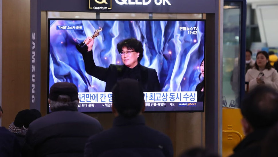 """People watch a TV screen showing images of South Korean director Bong Joon Ho at the Seoul Railway Station on February 10, 2020 in Seoul, South Korea. Bong Joon-ho's """"Parasite"""" has bagged four Oscar titles, becoming the first non-English language film to win best picture. (Photo by Chung Sung-Jun/Getty Images)"""
