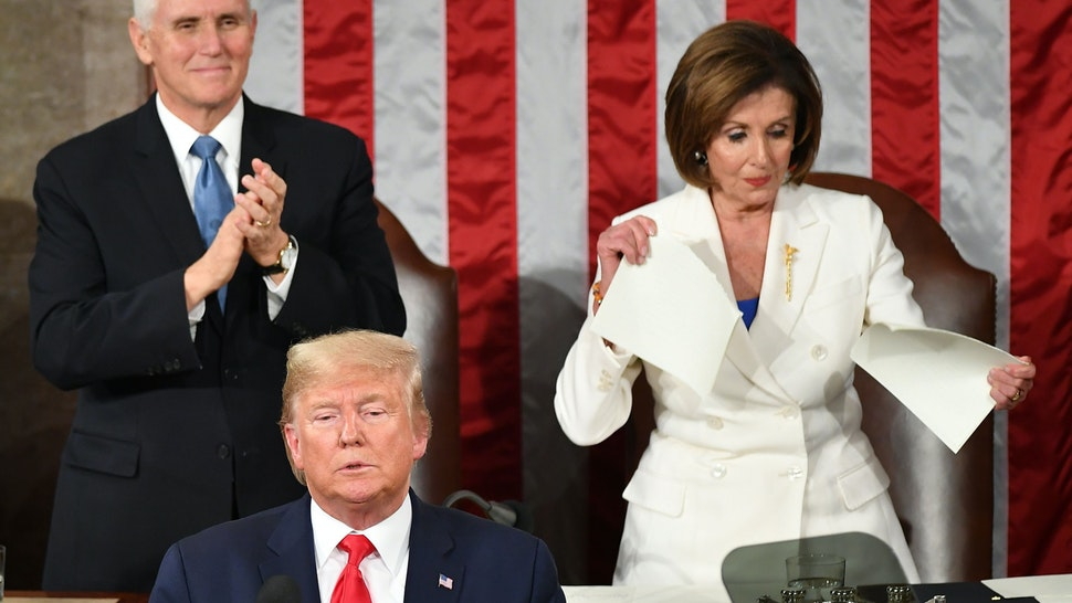 US Vice President Mike Pence claps as Speaker of the US House of Representatives Nancy Pelosi appears to rip a copy of US President Donald Trumps speech after he delivers the State of the Union address at the US Capitol in Washington, DC, on February 4, 2020.