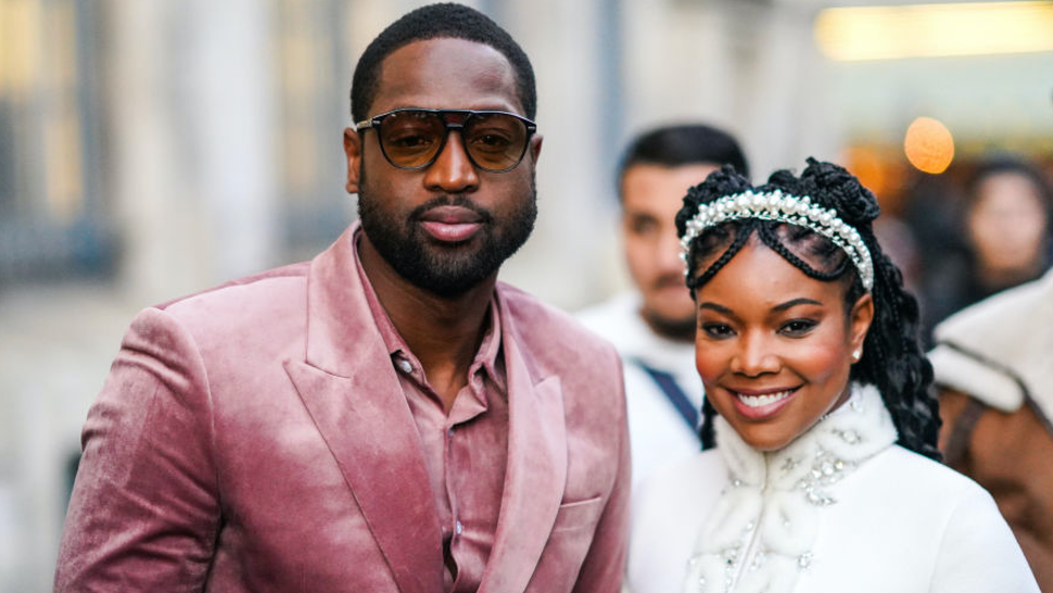 Dwayne Wade (L) wears sunglasses, a pink velvet shirt, a pink velvet jacket, a matched belt ; Gabrielle Union (R) wears a pearl headband, a white fluffy jacket with rhinestone embroideries, a mandarin collar and bell sleeves, outside Ralph & Russo, during Paris Fashion Week