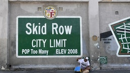 TOPSHOT - A man gestures while seated beside a Skid Row painting on a sidewalk in downtown Los Angeles on May 30, 2019. - The city of Los Angeles on May 29 agreed to allow homeless people on Skid Row to keep their property and not have it seized, providing the items are not bulky or hazardous.