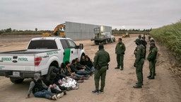 U.S. Border Patrol agents detain undocumented immigrants caught near a section of privately-built border wall under construction on December 11, 2019 near Mission, Texas. The hardline immigration group We Build The Wall is funding construction of the wall on private land along the Rio Grande, which forms the border with Mexico. The group, led by former Trump strategist Stephen Bannon claims to have raised tens of millions of dollars in a GoFundMe drive to build sections of wall along stretches of the U.S. southwest border with Mexico. (Photo by John Moore/Getty Images)