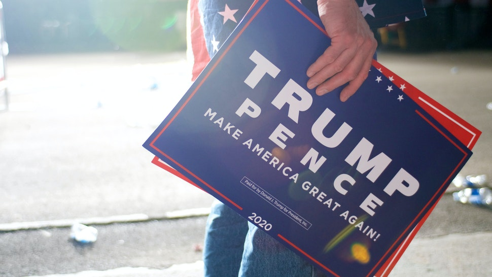 A supporters stands signs as US President Donald J Trump departs after speaking at a MAGA rally at the Williamsport Regional Airport, in Montoursville, PA on May 20, 2019.