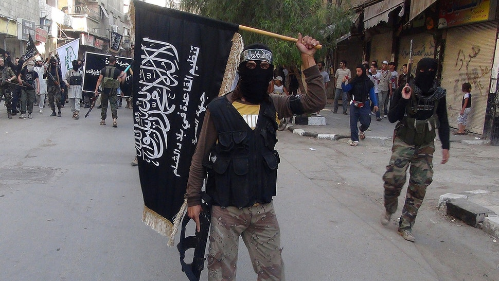 Islamic fighters from the al-Qaida group in the Levant, Al-Nusra Front, wave their movement's flag as they parade at the Yarmuk Palestinian refugee camp, south of Damascus, to denounce Israels military offensive on the Gaza Strip, on July 28, 2014. Israeli shells struck a UN school in Gaza early today, killing 16, as ground troops made a signficant push into the territory despite Palestinian efforts to broker a 24-hour truce. AFP PHOTO/RAMI AL-SAYED