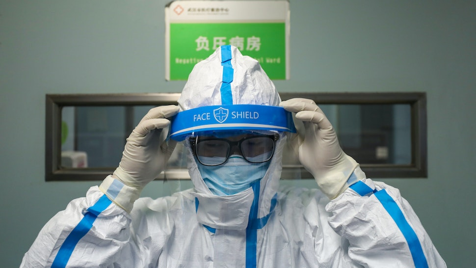 WUHAN, CHINA - FEBRUARY 13 2020: A doctor puts on the isolation outfit before entering the negative-pressure isolation ward in Jinyintan Hospital, designated for critical COVID-19 patients, in Wuhan in central China's Hubei province Thursday, Feb. 13, 2020. The city reported 13,436 new cases of COVID-19 Feb. 12, a big jump after the city combed communities for patients and expanded the capacity to take them in.