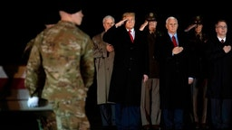 """US President Donald Trump (L) and Vice President Mike Pence (C) observe the dignified transfer of two US soldiers, killed in Afghanistan, at Dover Air Force Base in Dover, Delaware, on February 10, 2020 with . - The two soldiers have been identified as Sgt. 1st Class Javier Jaguar Gutierrez, 28, of San Antonio, TX, and Sgt. 1st Class Anonio Rey Rodriguez, 28, of Las Cruces, New Mexico. US and Afghan troops came under """"direct fire"""" in eastern Afghanistan late on February 8, a US military official said. (Photo by JIM WATSON / AFP) (Photo by"""