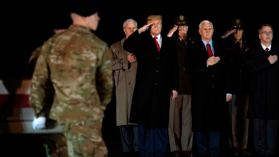 "US President Donald Trump (L) and Vice President Mike Pence (C) observe the dignified transfer of two US soldiers, killed in Afghanistan, at Dover Air Force Base in Dover, Delaware, on February 10, 2020 with . - The two soldiers have been identified as Sgt. 1st Class Javier Jaguar Gutierrez, 28, of San Antonio, TX, and Sgt. 1st Class Anonio Rey Rodriguez, 28, of Las Cruces, New Mexico. US and Afghan troops came under ""direct fire"" in eastern Afghanistan late on February 8, a US military official said. (Photo by JIM WATSON / AFP) (Photo by"