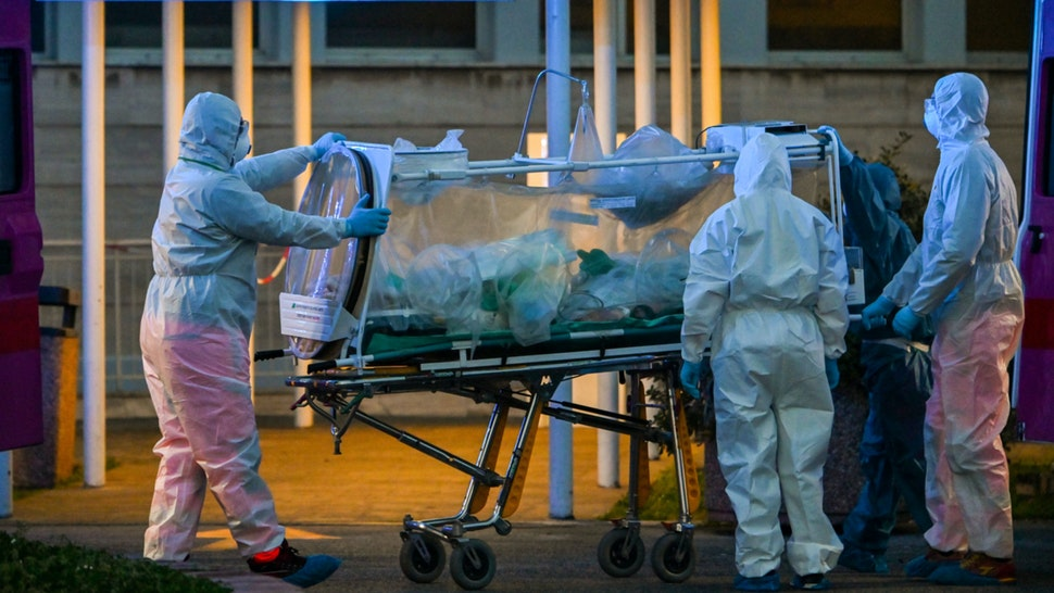 Medical workers in overalls stretch a patient under intensive care into the newly built Columbus Covid 2 temporary hospital to fight the new coronavirus infection, on March 16, 2020 at the Gemelli hospital in Rome.