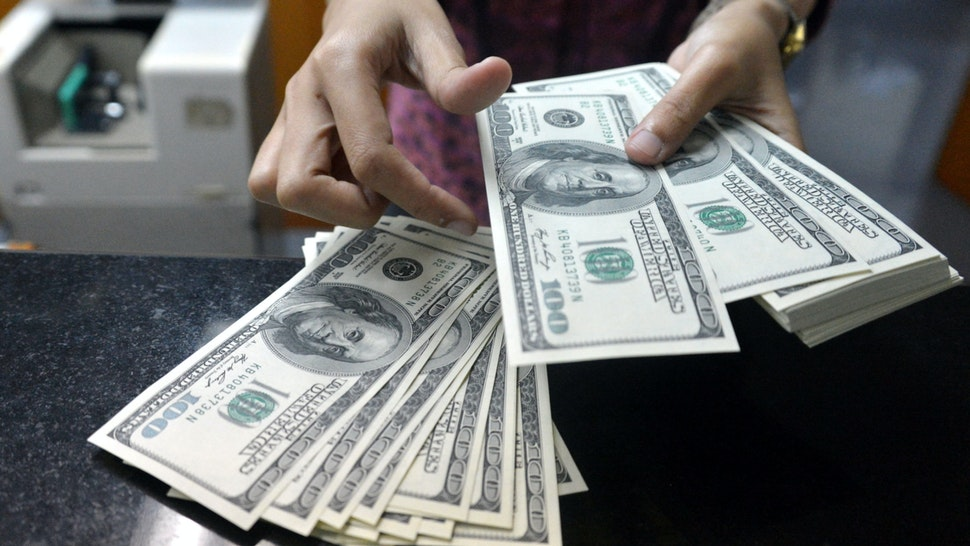 An employee counts USD notes at a money change outlet in Jakarta on June 14, 2013.