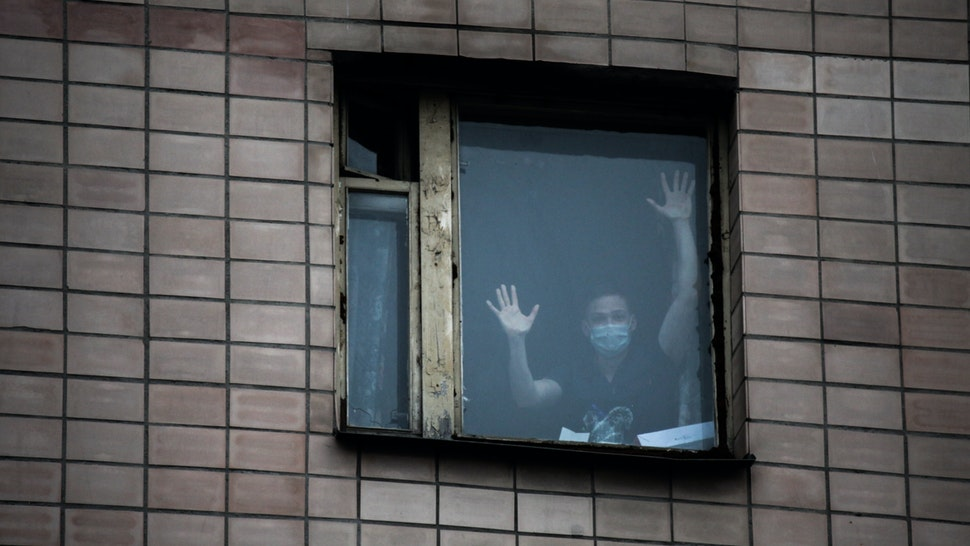 Student in a protective mask in the window of the quarantine building of educational premises and a hostel of the St. Petersburg Medical Academy in St. Petersburg The building is quarantined after the coronavirus was detected in a student who returned from Italy. 05 march 2020.