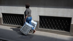 A women carries two large packs of toilet rolls into nearby offices, the capital's financial district, on 19th April, in the City of London, England.