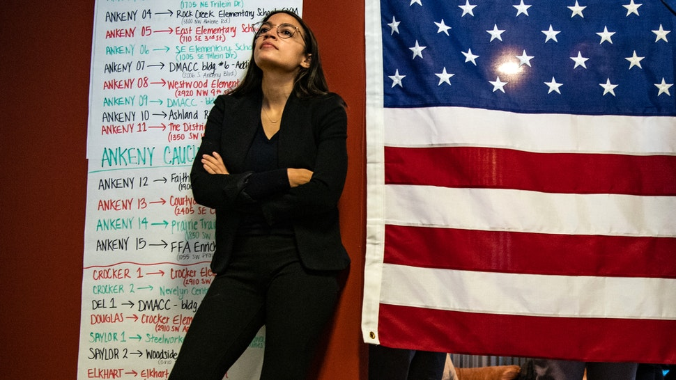 ANKENY, IOWA - JANUARY 26: Rep. Alexandria Ocasio-Cortez, D-N.Y. listens as Sen. Bernie Sanders, I-Vt., 2020 Democratic Presidential Candidate, speak to volunteers and supporters at Ankeny Field Office during a campaign stop on Sunday, January 26, 2020 in Ankeny, Iowa.