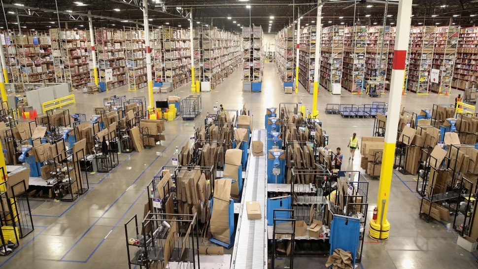 ROMEOVILLE, IL - AUGUST 01: Workers pack and ship customer orders at the 750,000-square-foot Amazon fulfillment center on August 1, 2017 in Romeoville, Illinois. On August 2, Amazon will be holding job fairs at several fulfillment centers around the country, including the Romeoville facility, in an attempt to hire more than 50,000 workers.