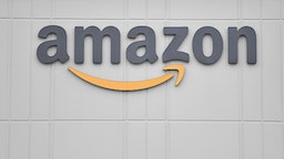 The logo of US online retail giant Amazon is seen at the distribution center in Staten Island as workers strike in demand that the facility be shut down and cleaned after one staffer tested positive for the coronavirus on March 30, 2020 in New York. - Amazon employees at a New York City warehouse walk off the job March 30, 2020, as a growing number of delivery and warehouse workers demand better pay and protections in the midst of the COVID-19 pandemic.