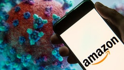 In this photo illustration the American electronic commerce and cloud computing company Amazon logo seen displayed on a smartphone with a computer model of the COVID-19 coronavirus on the background. (Photo Illustration by Budrul Chukrut/SOPA Images/LightRocket via Getty Images)