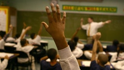 Students raise their hands to answer a teacher's question at the KIPP Academy in the South Bronx, part of a network of public middle schools that is becoming a model for educating poor children.