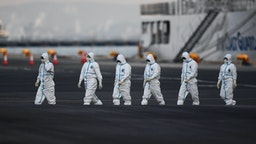 People wearing protective suits walk from the Diamond Princess cruise ship, with around 3,600 people quarantined onboard due to fears of the new coronavirus, at the Daikoku Pier Cruise Terminal in Yokohama port on February 10, 2020.