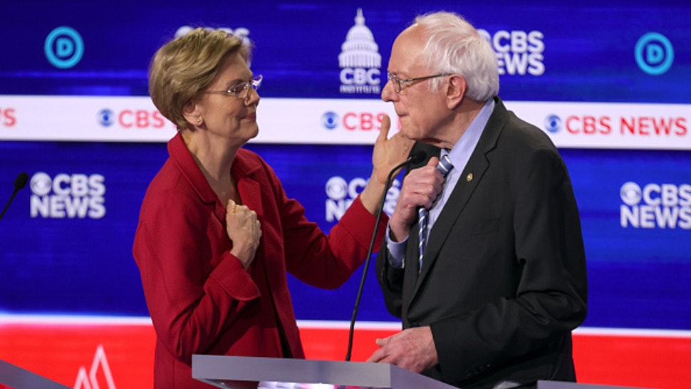 CHARLESTON, SOUTH CAROLINA - FEBRUARY 25: Democratic presidential candidates Sen. Elizabeth Warren (D-MA) (L) and Sen. Bernie Sanders (I-VT) interact during a break at the Democratic presidential primary debate at the Charleston Gaillard Center on February 25, 2020 in Charleston, South Carolina. Seven candidates qualified for the debate, hosted by CBS News and Congressional Black Caucus Institute, ahead of South Carolina's primary in four days.
