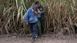 MISSION, TEXAS - DECEMBER 11: A U.S. Border Patrol agent detains undocumented immigrants caught in a sugar cane field near a section of privately-built border wall under construction on December 11, 2019 near Mission, Texas. The hardline immigration group We Build The Wall is funding construction of the wall on private land along the Rio Grande, which forms the border with Mexico. The group, led by former Trump strategist Stephen Bannon claims to have raised tens of millions of dollars in a GoFundMe drive to build sections of wall along stretches of the southwest border with Mexico.