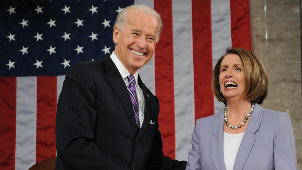 US Vice-President Joe Biden (L) and Speaker of the House Nancy Pelosi shake hands as President Barack Obama enters the room to deliver his first State of the Union speech to a joint session of Congress in Washington on January 27, 2010.