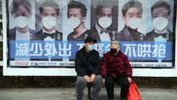 A man and woman sit in front of a poster reminding citizens to wear face masks as a preventive measure against the COVID-19 coronavirus, at a bus stop in Bozhou, in China's eastern Anhui province on March 6, 2020. - China reported 30 more deaths from the new coronavirus outbreak on March 6, with fresh infections rising for a second straight day and 16 new cases imported from overseas. (Photo by STR / AFP)