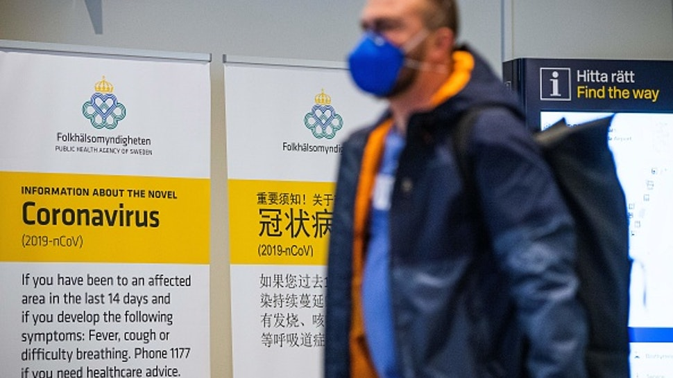 A passenger arriving in Stockholm's Arlanda airport is greeted by signs produced by the public health agency advising travelers what to do if they show symptoms of infection by the new coronavirus after arriving in Sweden on March 5, 2020.